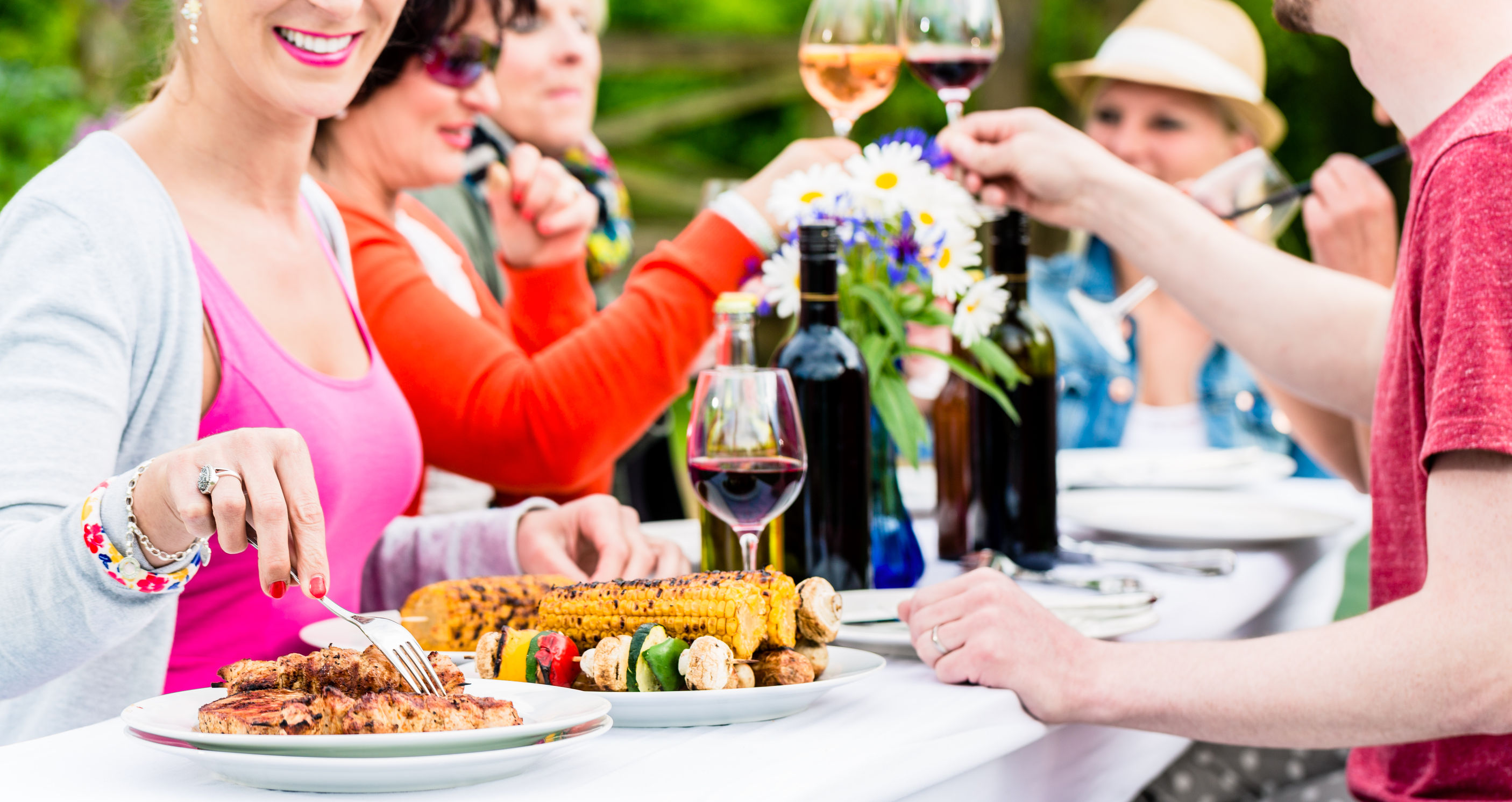 42876117 - women and men celebrating garden party, eating and drinking together